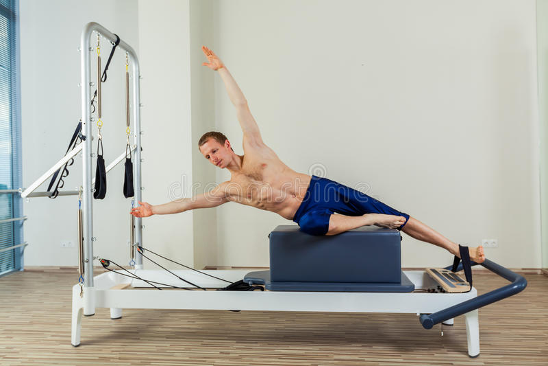 El entrenamiento del reformador de Pilates ejercita al hombre en el gimnasio interior fotografía de archivo