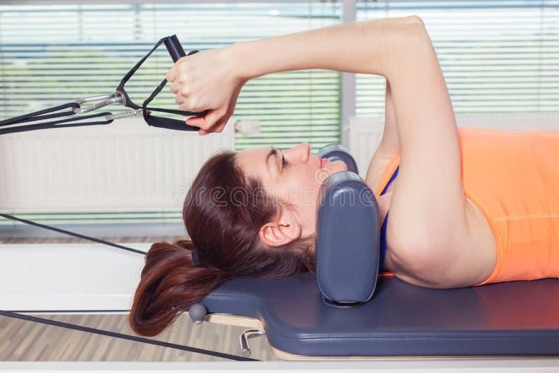 El entrenamiento del reformador de Pilates ejercita a la mujer en el gimnasio interior imagen de archivo