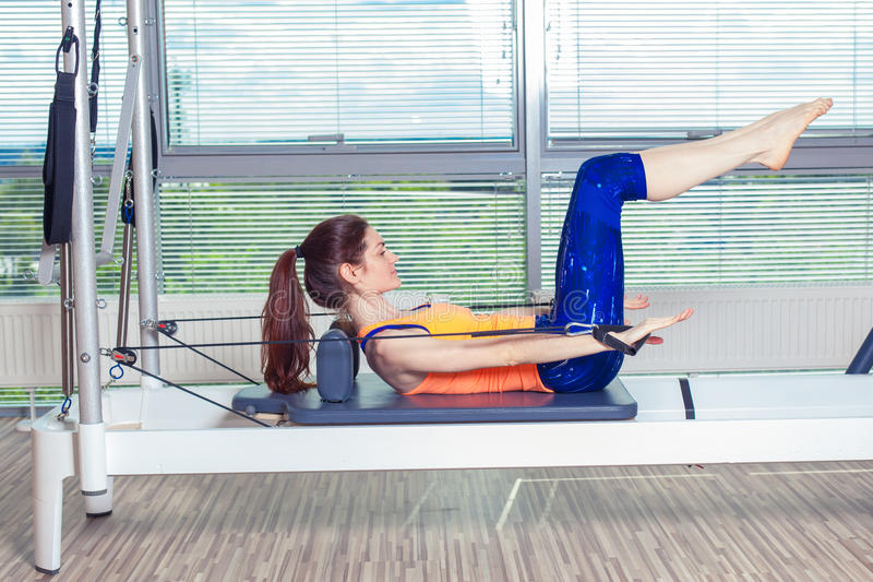 El entrenamiento del reformador de Pilates ejercita a la mujer en el gimnasio interior imágenes de archivo libres de regalías