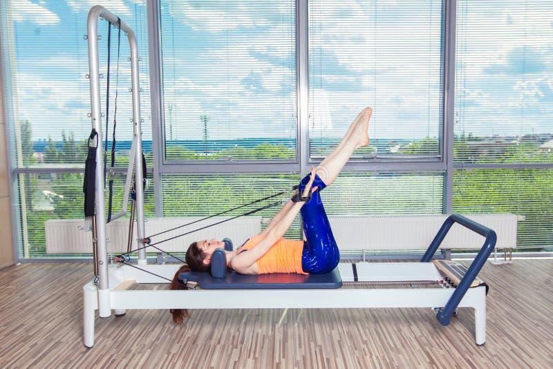 El entrenamiento del reformador de Pilates ejercita a la mujer en el gimnasio interior foto de archivo libre de regalías