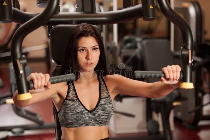 El entrenamiento deportivo activo de la mujer arma en gimnasio del club de fitness foto de archivo