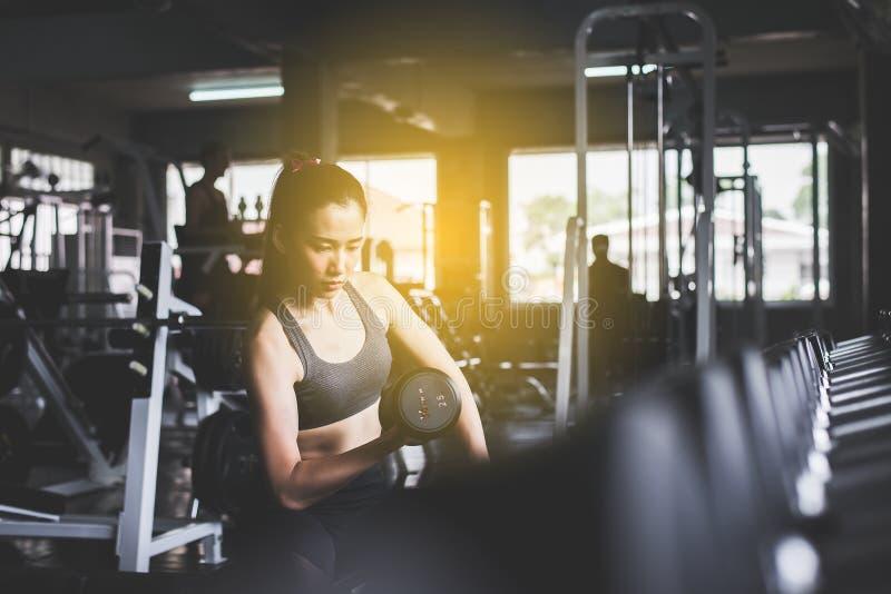 El entrenamiento hermoso asiático deportivo de la mujer con la pesa de gimnasia, hembra en ropa de deportes hace los ejercicios e foto de archivo libre de regalías