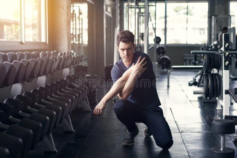 El entrenamiento hermoso del ejercicio del hombre en la fractura de la aptitud del gimnasio se relaja y calentar con la pesa de g imagen de archivo libre de regalías