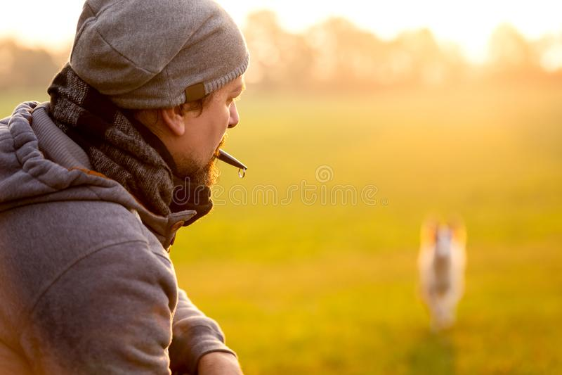 El entrenamiento y la obediencia con un silbido del perro, hombre es recordar su animal doméstico fotografía de archivo libre de regalías
