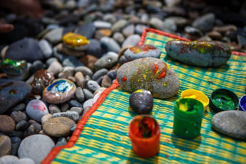 El entretenimiento de los niños en piedras de una playa-pintura del guijarro fotografía de archivo