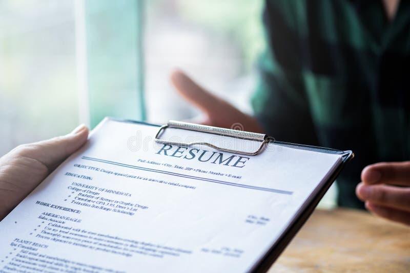 El entrevistador que lee un curriculum vitae, persona presenta la solicitud de trabajo, persona para describirse al entrevistador foto de archivo