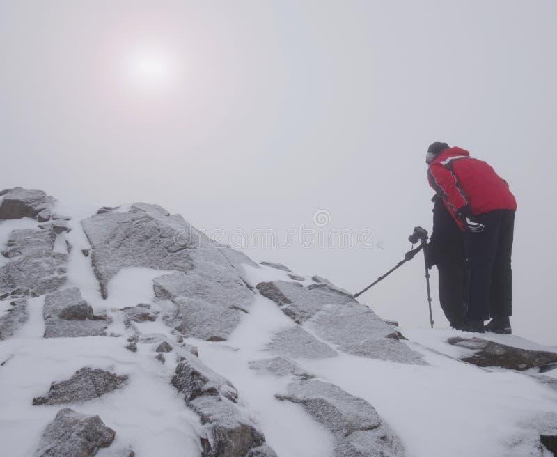 El entusiasta del caminante y de la foto permanece en pico nevoso en el trípode Hombres en el acantilado que habla y que piensa imagen de archivo