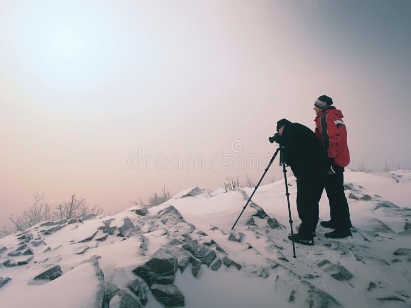 El entusiasta del caminante y de la foto permanece en pico nevoso en el trípode Hombres en el acantilado que habla y que piensa fotografía de archivo