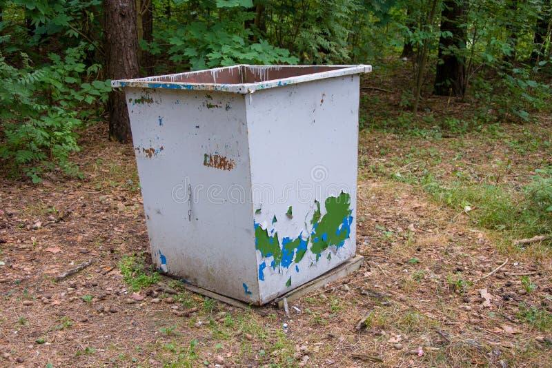 El envase para recoger la basura en un parque de la ciudad, recogiendo la ruina ambiental imagenes de archivo