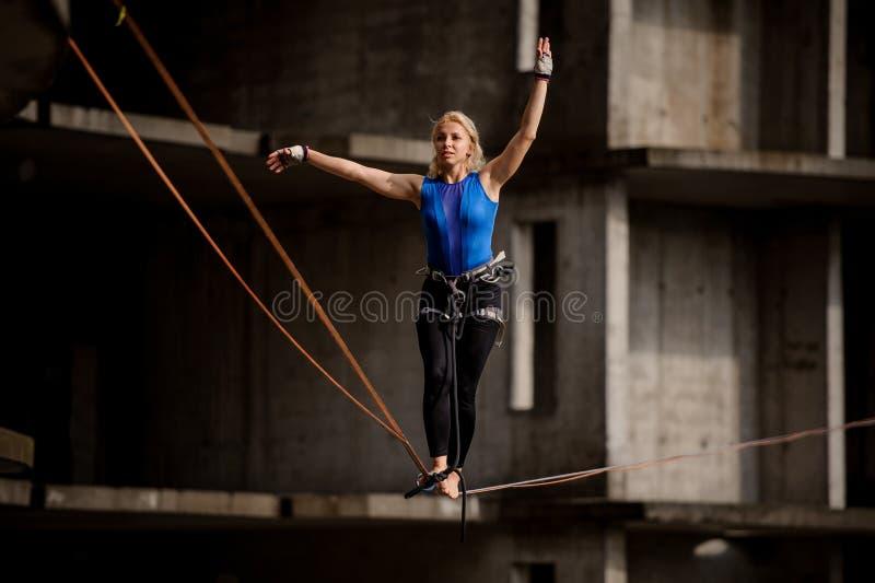 El equilibrist femenino profesional que equilibraba con los brazos aumentó en el slackline imágenes de archivo libres de regalías