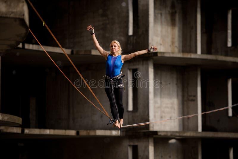 El equilibrist femenino que equilibraba con los brazos aumentó en la cuerda del slackline imagen de archivo libre de regalías