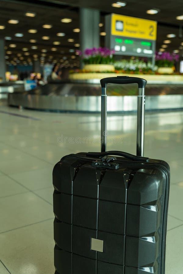 El equipaje de mano perdido del rodillo del hardshell negro se fue desatendido en el área de la recuperación de equipaje en el ae fotos de archivo libres de regalías