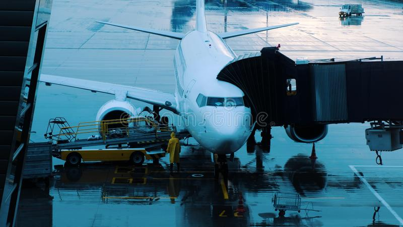 El equipaje se mueve a lo largo de la banda transportadora al aeroplano en tiempo lluvioso fotos de archivo