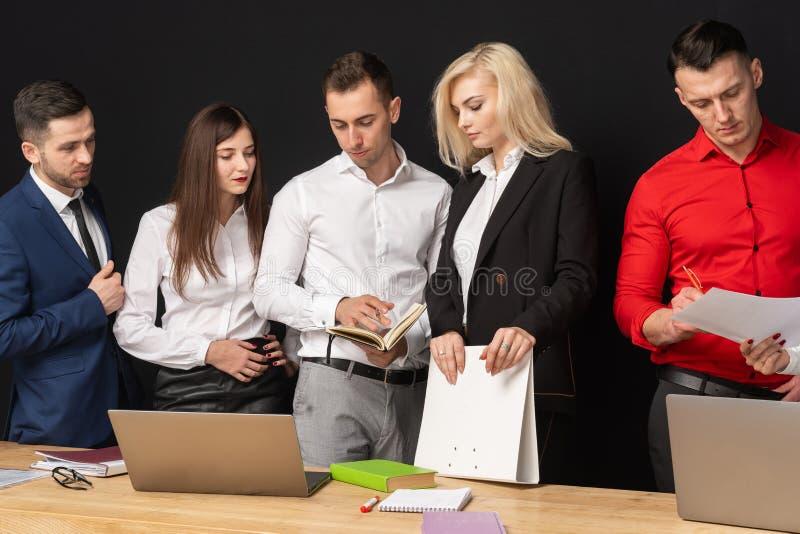 El equipo amistoso del bisiness tiene trabajo en la oficina usando el ordenador portátil en la tabla imagen de archivo libre de regalías