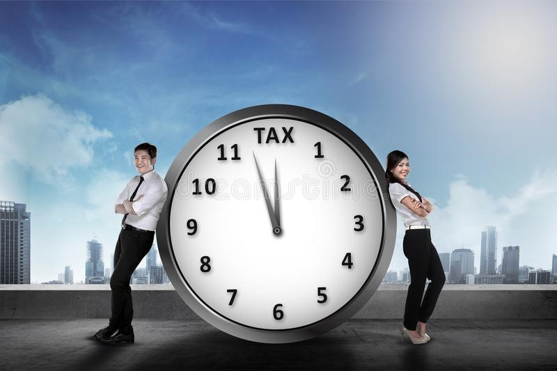 El equipo asiático sonriente del negocio se inclina detrás en el reloj con la muestra del impuesto fotografía de archivo