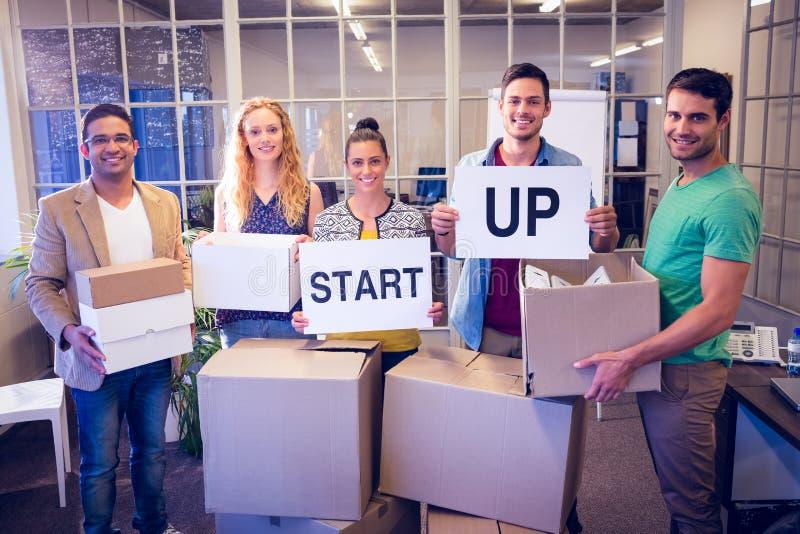 El equipo creativo del negocio que sostiene la cartulina escrita empieza para arriba fotos de archivo libres de regalías