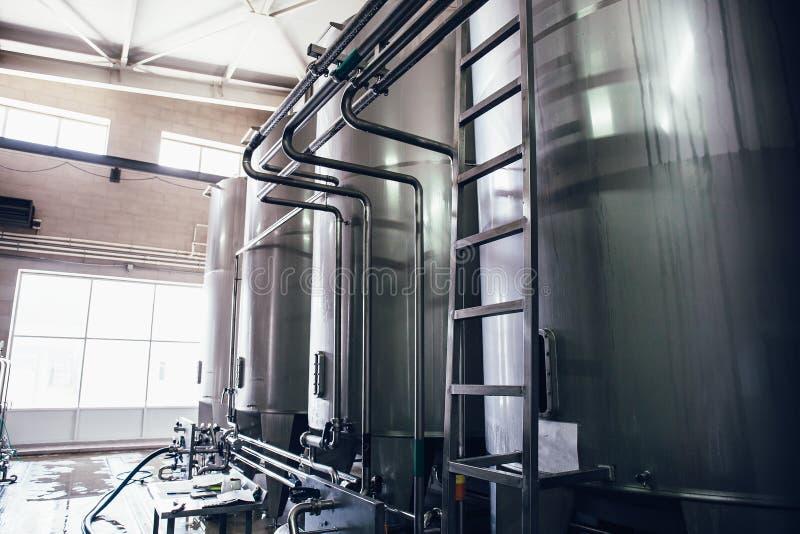 El equipo de acero inoxidable de la fábrica del jugo, los depósitos o los tanques grandes y los tubos en moderno plat Fondo indus fotos de archivo libres de regalías