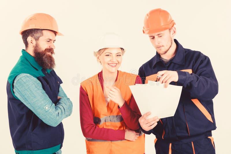 El equipo de arquitectos, ingenieros discute, las miradas en el documento, fotos de archivo libres de regalías