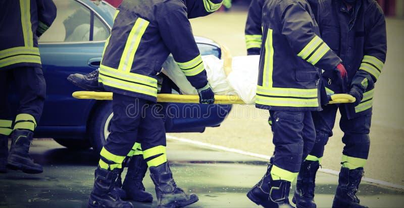 El equipo de bomberos rescató herido después de un acci trágico del coche foto de archivo