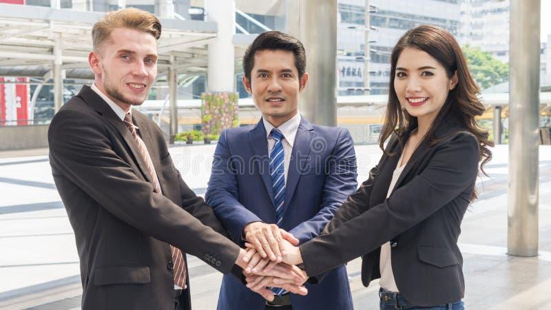 El equipo de hombres de negocios del hombre y mujer elegantes se une a la mano al sho imagen de archivo