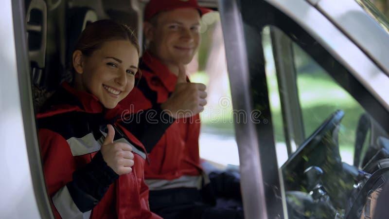 El equipo de la ambulancia que muestra los pulgares para arriba, los profesionales de servicio proporciona los primeros auxilios imagen de archivo libre de regalías