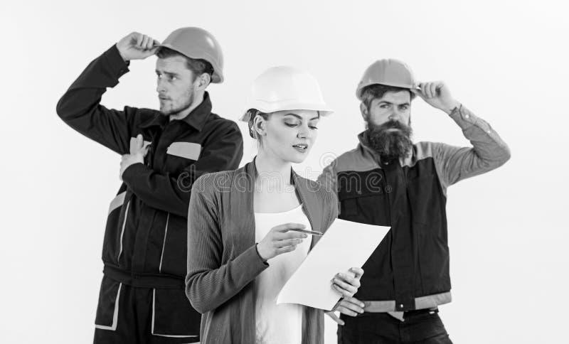 El equipo de los arquitectos, constructores con el encargado de la mujer mira el documento fotografía de archivo libre de regalías