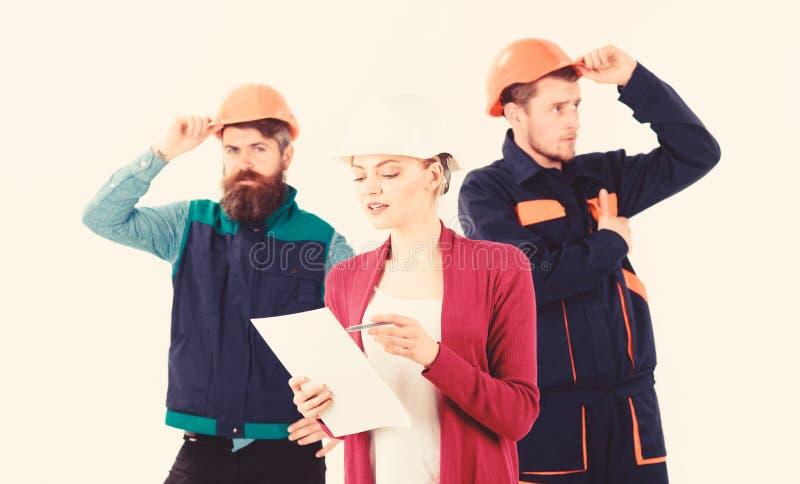 El equipo de los arquitectos, constructores con el encargado de la mujer mira el documento imágenes de archivo libres de regalías