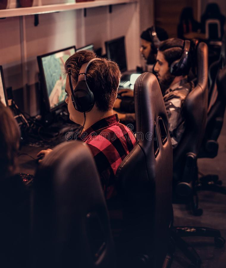 El equipo de videojugadores adolescentes juega en un videojuego multijugador en la PC en un club del juego imagenes de archivo