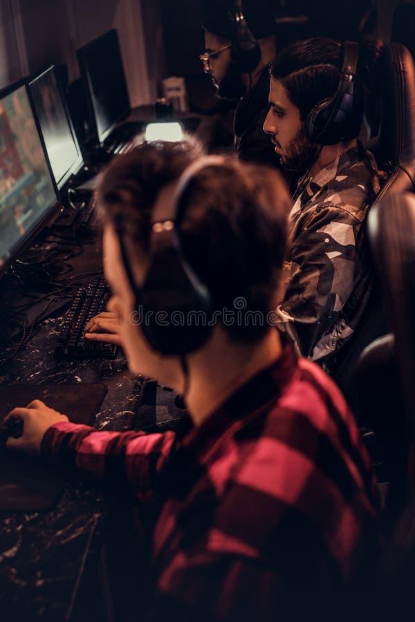 El equipo de videojugadores adolescentes juega en un videojuego multijugador en la PC en un club del juego foto de archivo libre de regalías