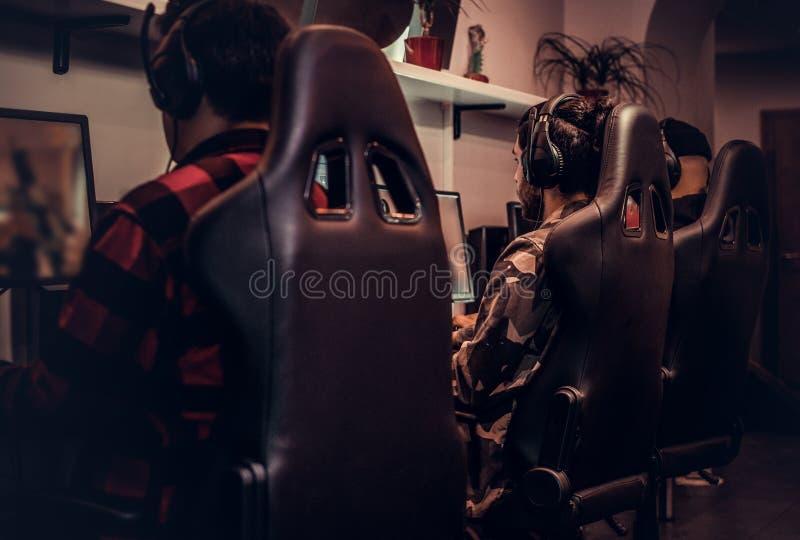 El equipo de videojugadores adolescentes juega en un videojuego multijugador en la PC en un club del juego fotografía de archivo