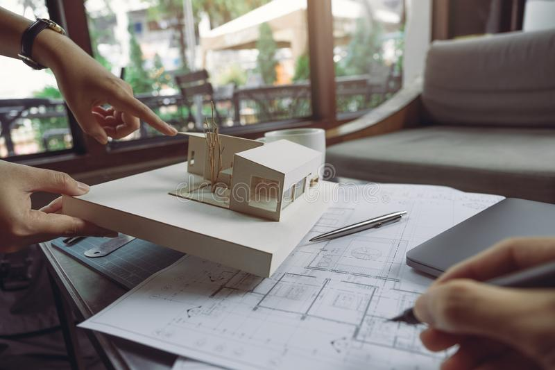 El equipo del colega de arquitectos que discuten y que señalan en el modelo de la arquitectura con el papel de dibujo de la tiend fotografía de archivo