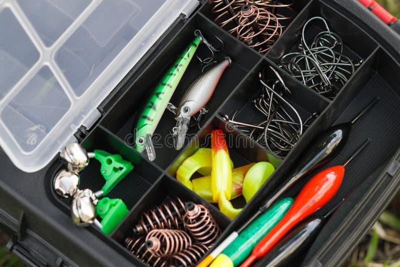 El equipo del diverso pescador en una caja de aparejos plástica fotografía de archivo libre de regalías