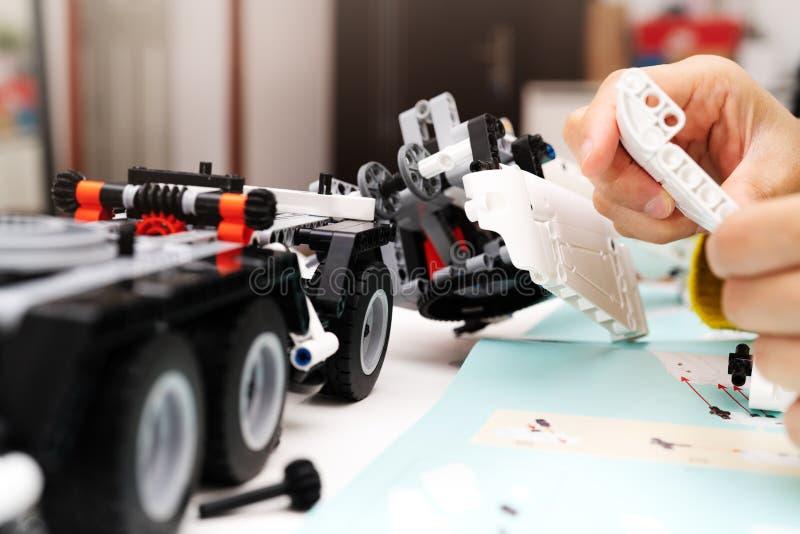 El equipo del montaje del coche, mujer monta un juguete muy complicado y común del coche camión foto de archivo