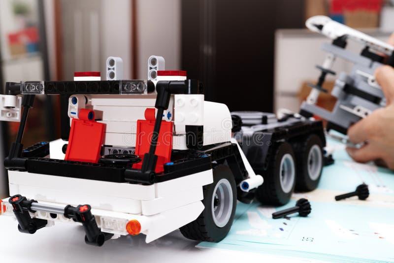 El equipo del montaje del coche, mujer monta un juguete muy complicado y común del coche camión fotos de archivo