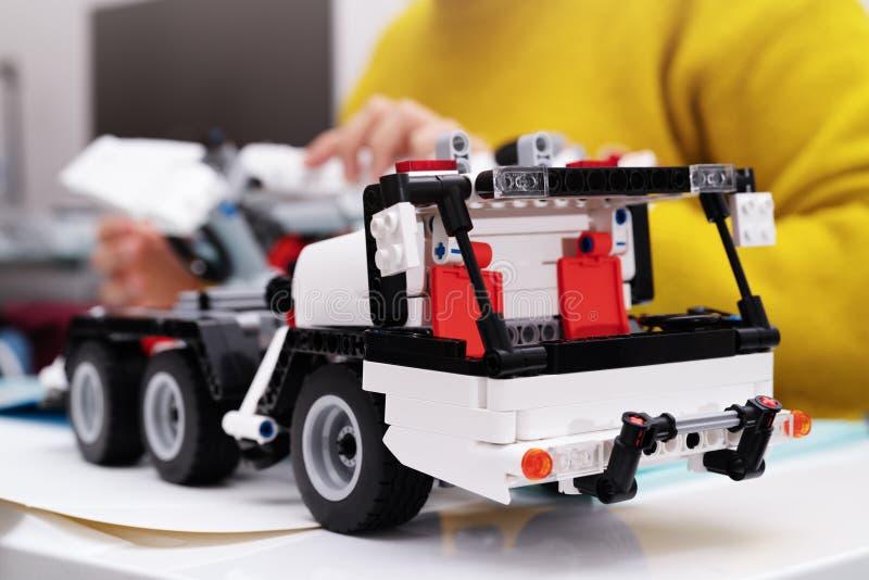 El equipo del montaje del coche, mujer monta un juguete muy complicado y común del coche camión foto de archivo libre de regalías