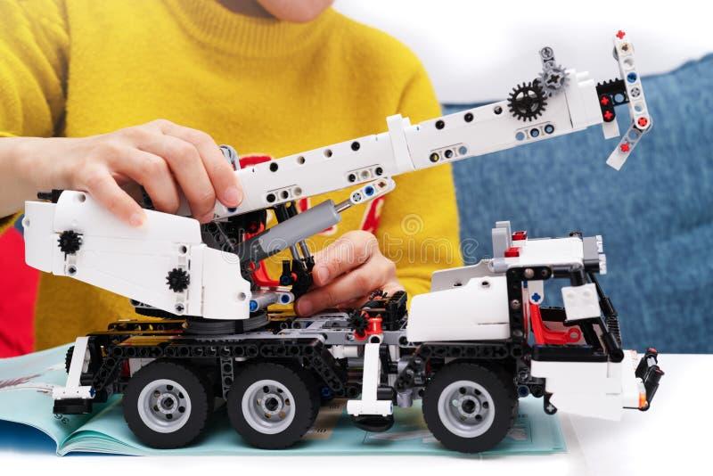 El equipo del montaje del coche, mujer monta un juguete muy complicado y común del coche camión imagen de archivo
