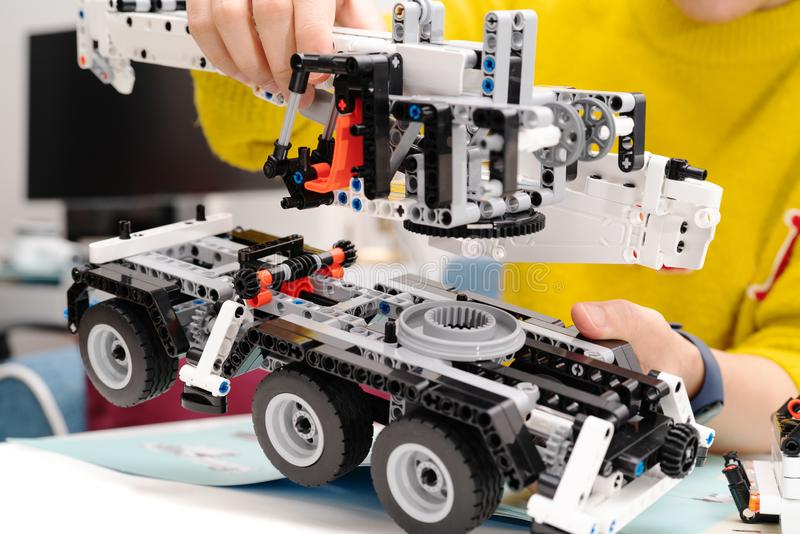 El equipo del montaje del coche, mujer monta un juguete muy complicado y común del coche camión fotografía de archivo