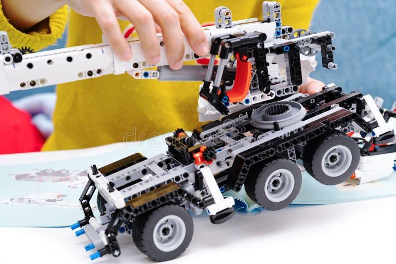 El equipo del montaje del coche, mujer monta un juguete muy complicado y común del coche camión fotografía de archivo libre de regalías