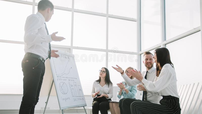 El equipo del negocio aplaude el altavoz en un informe en la nueva oficina imagen de archivo