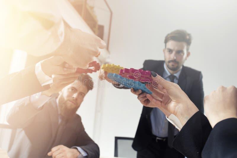 El equipo del negocio conecta pedazos de engranajes Trabajo en equipo, sociedad y concepto de la integraci?n foto de archivo