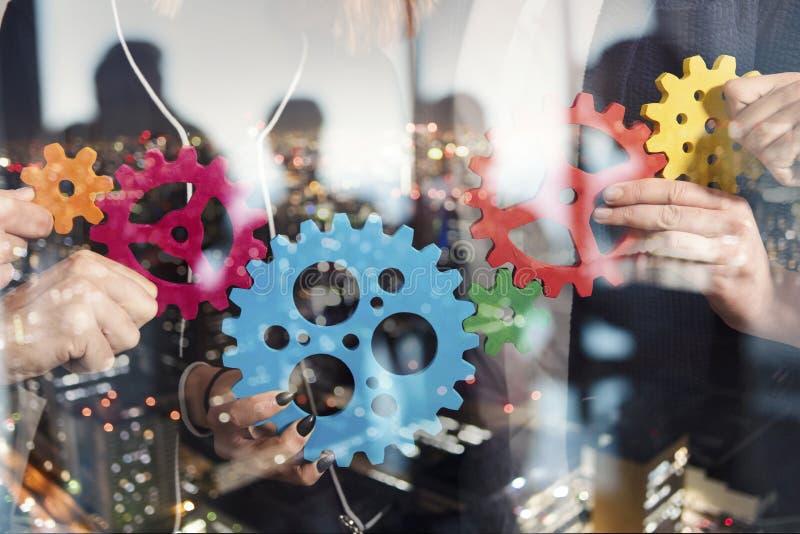 El equipo del negocio conecta pedazos de engranajes Trabajo en equipo, sociedad y concepto de la integraci?n Exposici?n doble foto de archivo