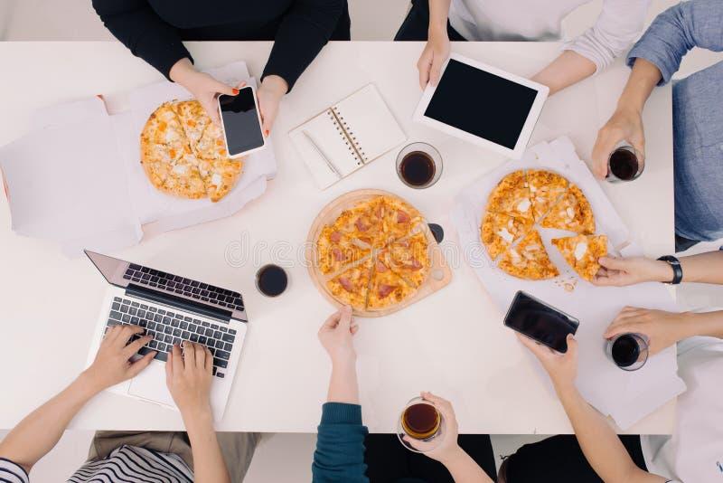 El equipo del negocio est? comiendo la pizza en el trabajo mientras que trabaja fotografía de archivo libre de regalías