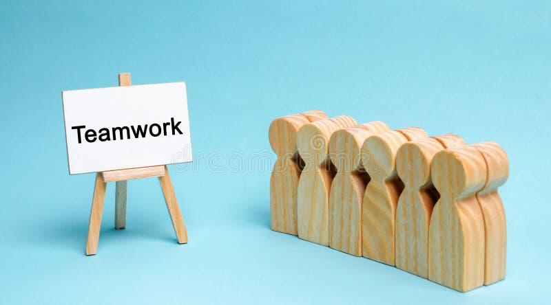 El equipo del negocio se está colocando cerca de la lona con el trabajo en equipo de la palabra Concepto del trabajo en equipo El imagenes de archivo