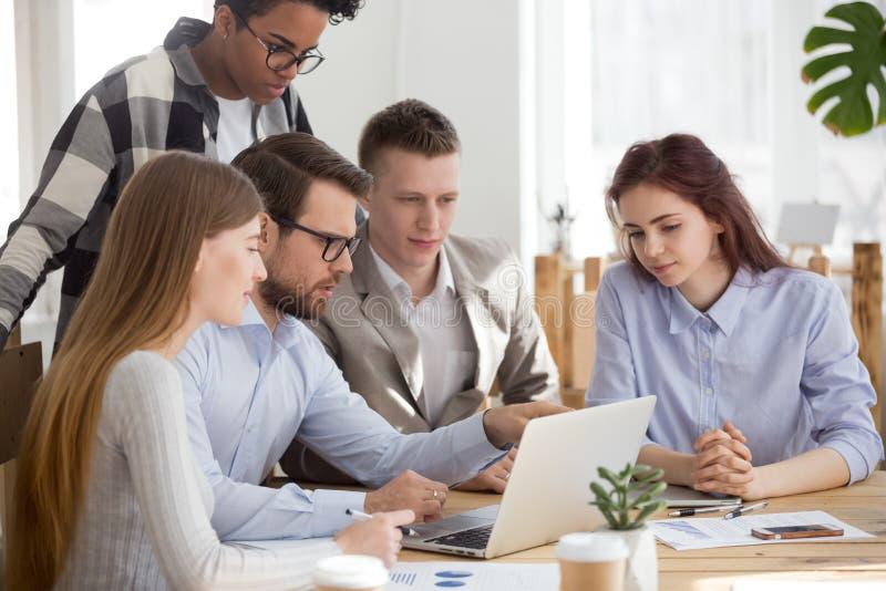 El equipo diverso del negocio escucha el entrenamiento ejecutivo para explicar tarea del ordenador foto de archivo