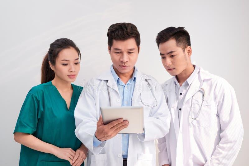 El equipo médico incluye los doctores y a la enfermera que miran un ipad/una tableta junto foto de archivo libre de regalías