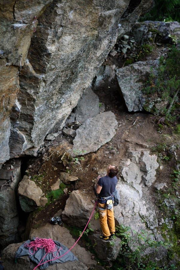 El equipo que sube que lleva del hombre joven que se coloca delante de una roca de piedra al aire libre y se prepara para subir,  fotografía de archivo libre de regalías