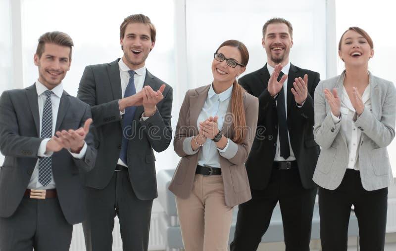 El equipo sonriente del negocio aplaude su éxito fotos de archivo libres de regalías