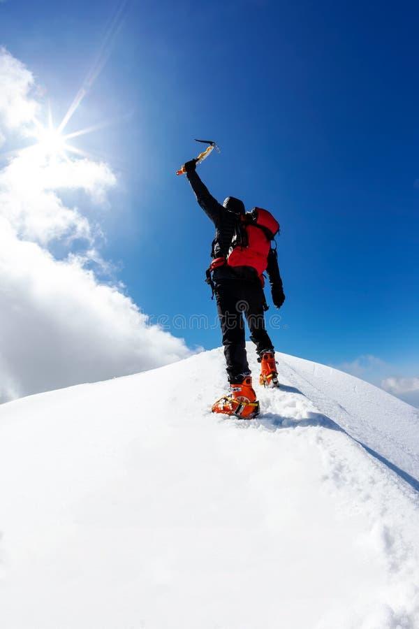 El escalador alcanza la cima de una montaña nevada imagen de archivo