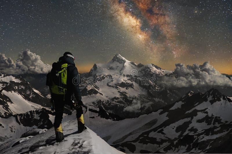 El escalador de la foto de la noche se coloca encima de una montaña en la nieve y mira las montañas circundantes sobre las cuales fotografía de archivo libre de regalías
