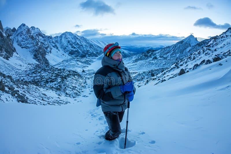 El escalador de la mujer en casco y abajo chaqueta con los palillos del senderismo va cuesta arriba en el amanecer imagen de archivo libre de regalías